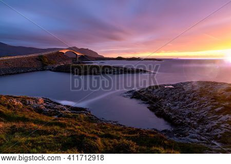 Vibrant Sunset Illuminates The Arch Of The Famous Great Atlantic Highway In Northern Norway. Long Ex