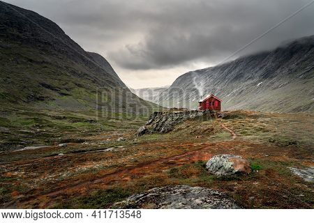 A Single Small Red Cabin Billows Smoke From It's Tiny Chimney In The Remote Gorge Of Central Norway.