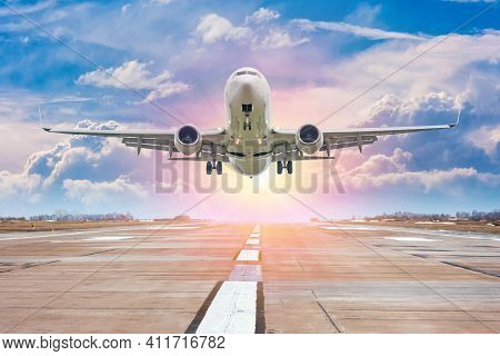 White Passenger Airplane Take Off From Airport Runway Against The Backdrop Of A Picturesque Evening