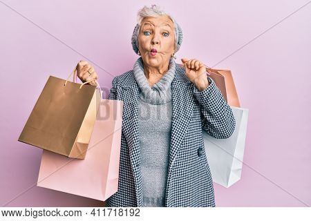 Senior grey-haired woman holding shopping bags making fish face with mouth and squinting eyes, crazy and comical.
