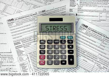 Stress Text On Business Calculator Screen With 1040 Internal Revenue Tax Forms