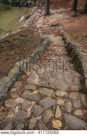 Old Stone And Rock Stairway Set In Cement Descending Downhill To The Beach Area At The Lake With The