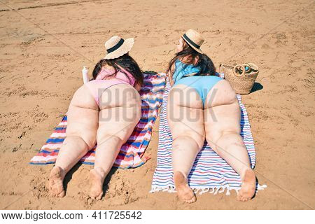 Backview of two plus size overweight sisters twins women relaxing lying on a towel at the beach on summer holidays