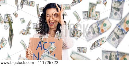 Young beautiful hispanic woman holding act now banner smiling happy doing ok sign with hand on eye looking through fingers
