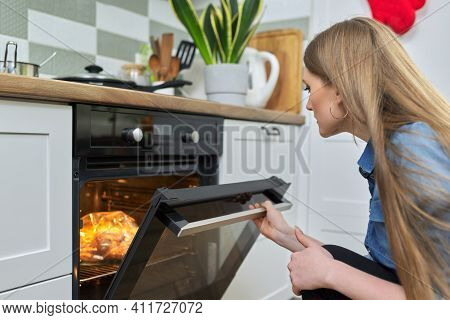Cooking At Home, Roasting Meat In Oven, Young Woman Putting Marinated Chicken In Baking Bag In Oven,