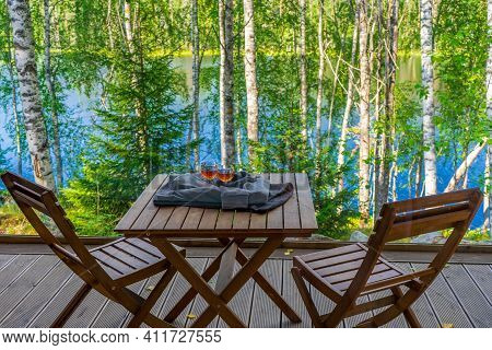 View From Panoramic Cottage Window To Outdoor Terrace With Table And Chairs Against Beautiful Landsc