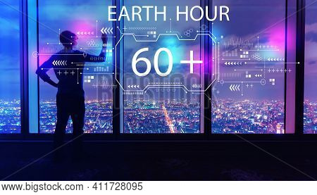 Earth Hour With Man Writing On Large Windows High Above A Sprawling City At Night