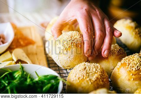 Homemade buns with sesame seeds. A woman's hand reaches for a roll, a table with breakfast