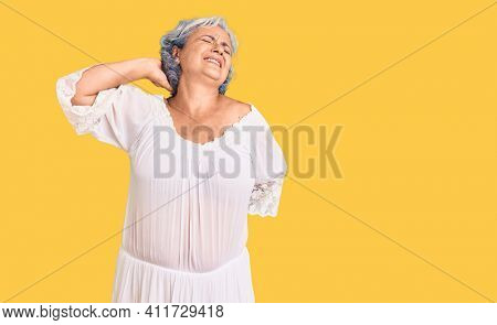 Senior woman with gray hair wearing bohemian style suffering of neck ache injury, touching neck with hand, muscular pain