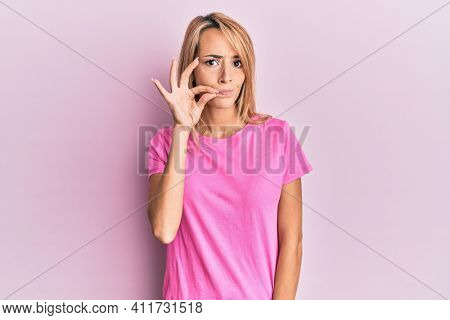 Beautiful blonde woman wearing casual pink tshirt mouth and lips shut as zip with fingers. secret and silent, taboo talking