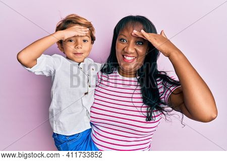 Hispanic family of mother and son hugging together with love stressed and frustrated with hand on head, surprised and angry face