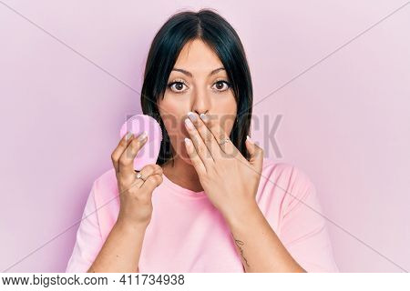 Young hispanic woman using facial exfoliating cleaner covering mouth with hand, shocked and afraid for mistake. surprised expression