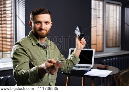 Caucasian Man Holding A Credit Card To Camera And Personal Wallet. Wireless Opened Computer In Backg