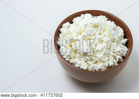 Cottage Cheese On A White Background. Homemade Cottage Cheese In A Deep Plate. Milk Product