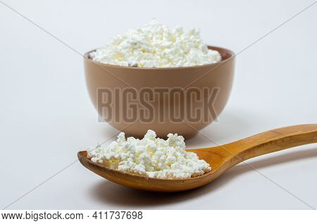 Cottage Cheese On A White Background. Homemade Cottage Cheese In A Deep Plate, Next To A Wooden Spoo