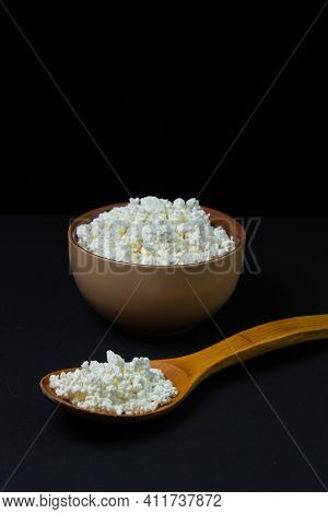 Curd On A Black Background. Homemade Cottage Cheese In A Deep Plate, Next To A Wooden Spoon With Cot