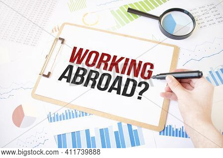 Text Working Abroad On White Paper Sheet And Marker On Businessman Hand On The Diagram. Business Con