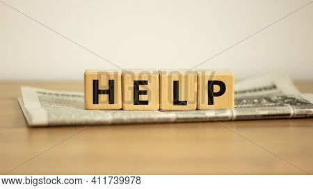 Support And Help Symbol. Wooden Cubes With The Word 'help'. Newspaper. Business, Psychology, Support