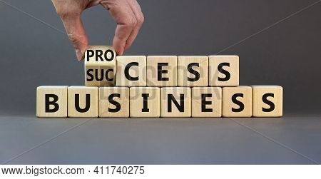 Success Business Process Symbol. Businessman Turns Wooden Cubes And Changes The Word 'success Busine
