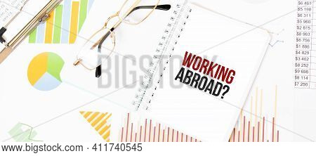 Text Working Abroad On White Notepad, Glasses, Graphs And Diagrams.