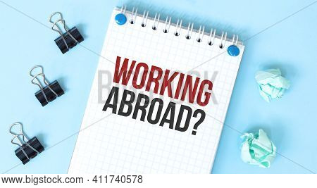 White Notepad With Text Working Abroad And Office Tools On The Blue Background