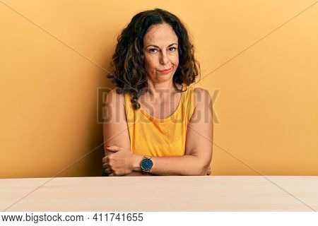 Beautiful middle age woman wearing casual clothes sitting on the table skeptic and nervous, disapproving expression on face with crossed arms. negative person.