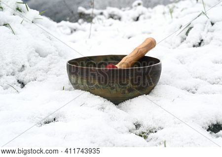 A Copper Tibetan Bowl In Winter.translation Of Mantra Transform Your Impure Body, Speech And Mind