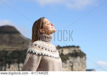 Side View Portrait Of A Relaxed Woman Breathing Fresh Air In Winter In The Mountain