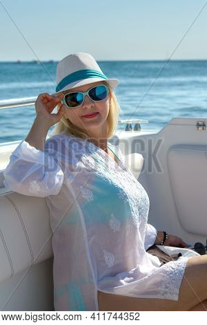 Blonde In A Hat And Dark Glasses Poses On A White Yacht