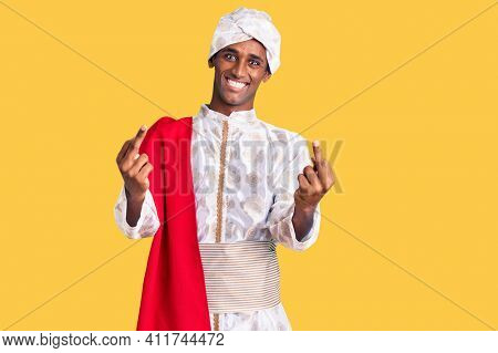 African handsome man wearing tradition sherwani saree clothes showing middle finger doing fuck you bad expression, provocation and rude attitude. screaming excited