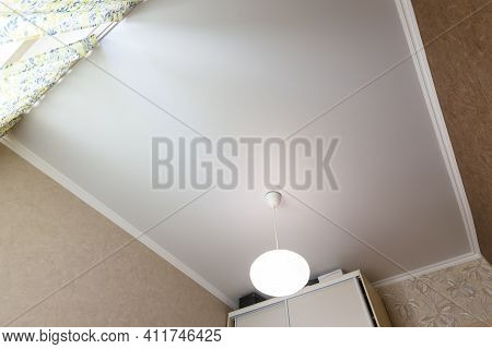 Stretch White Matte Ceiling Close-up With A Chandelier In The Interior Of A Rectangular Room