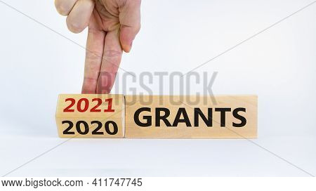 Business Concept Of Grants 2021. Businessman Flips Wooden Cube And Change Words 'grants 2020' To 'gr