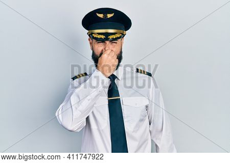 Young hispanic man wearing airplane pilot uniform smelling something stinky and disgusting, intolerable smell, holding breath with fingers on nose. bad smell