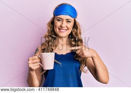 Young blonde girl wearing sleep mask and pyjama drinking coffee smiling happy pointing with hand and finger