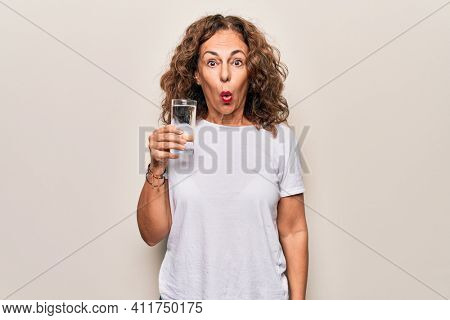 Middle age beautiful woman drinking glass of water to refreshment over white background scared and amazed with open mouth for surprise, disbelief face