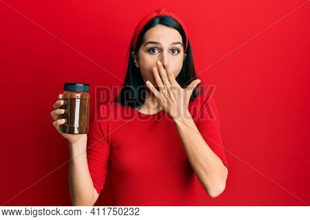 Young hispanic woman holding soluble coffee covering mouth with hand, shocked and afraid for mistake. surprised expression