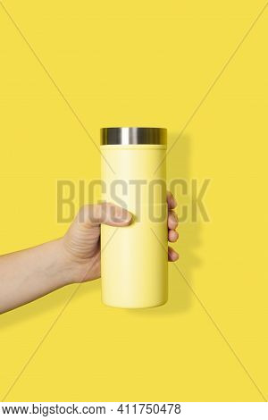 Hand Holds Yellow Travel Mug Isolated On White Background. Thermo Cup Or Tumbler In Female Hand.