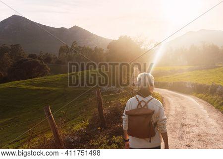 Older Woman From Behind Doing Hiking. Pensioner Enjoying Her Retirement. Elderly Activities.