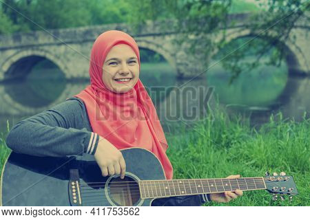 Happy Muslim Girl Traying To Play Acoustic Guitar On The River Bank  With The Bridge In The Backgrou