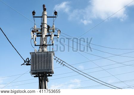 High Voltage Transformer Mounted On A Pole On Blue Sky Background At Sunny Day