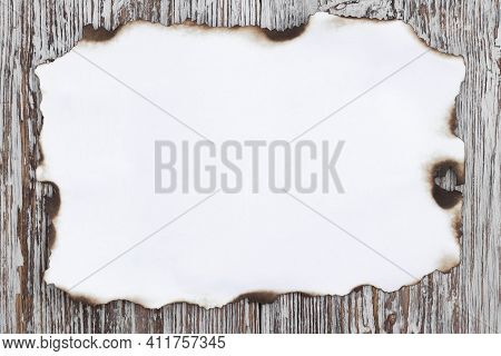 White Charred Sheet Of Paper On A Light Wooden Background