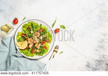 Salad With Baked Salmon Fish. Green Salad Mix With Tomatoes Anf Salmon. Top View At White Table.