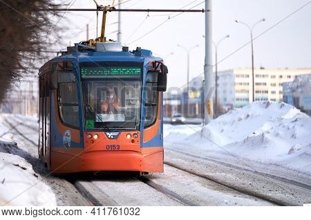 Russia, Naberezhnye Chelny, March 9, 2021: A Tram Rides On A Snow-covered Street. A Woman In A Medic