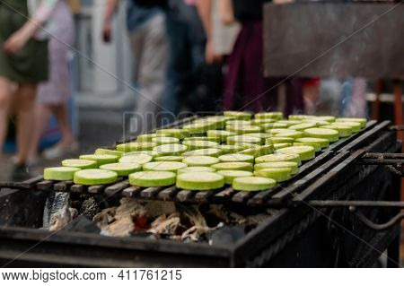 Close Up: Process Of Cooking Fresh Green Zucchini Slices On Grill At Summer Local Food Market. Outdo