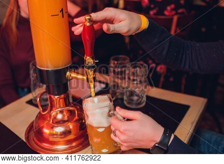 The Male Bartender Pouring Beer Into A Glass Close-up. Street Food. A Glass With Cold Beer In The Ba