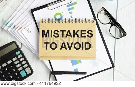Notepad With Text Mistakes To Avoid Lying On Financial Tables With A Pen. Business And Financial Con