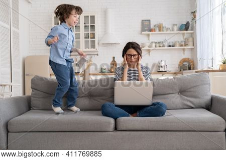 Irritated Mother Sitting On Couch Working On Laptop At Home, Distracted From Noise And Touching Her
