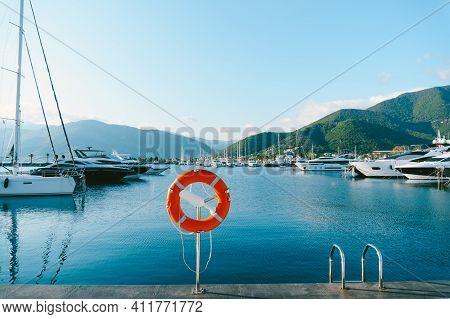 Orange Lifebuoy On A Chrome Base, On The Marina In Porto Montenegro, An Elite Area In Montenegro, Th