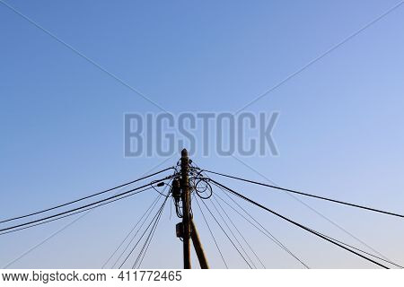 Old Wooden Pole, With A Wiring Harness, Power Lines, Telephone, Cable Tv Against A Blue Sky. A Mess