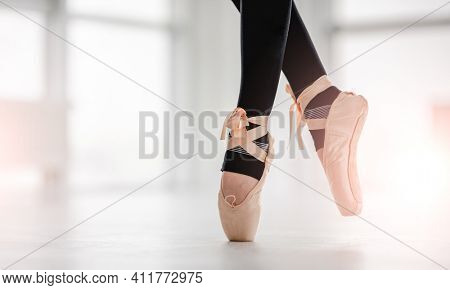 Closeup view on beautiful ballerina legs wearing black leggings and beige pointe shoes, staying on tiptoes in sunny dance studio